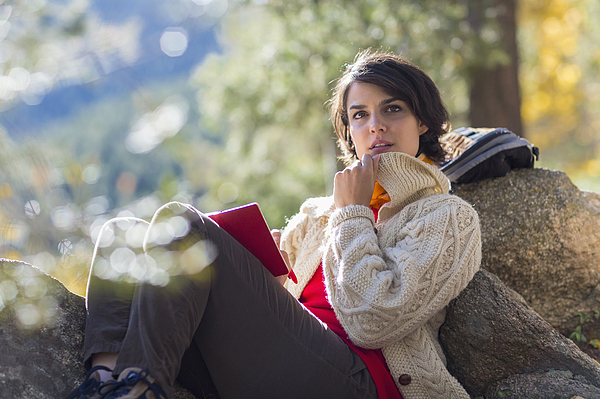 Mixed race hiker reading in forest Photograph by Marc Romanelli
