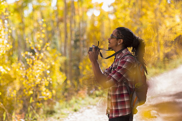 Mixed race hiker taking photograph in forest Photograph by Marc Romanelli