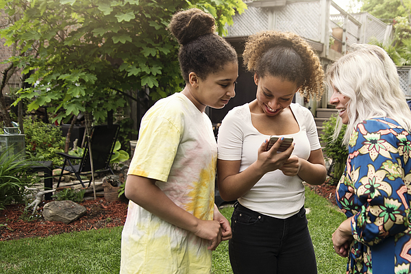 Mixed-race sisters looking at mobile phone with mother in backyard. Photograph by Martinedoucet