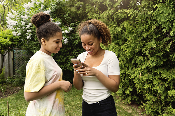 Mixed-race teenage sisters looking at mobile phone in backyard. Photograph by Martinedoucet