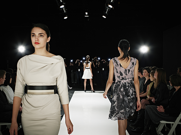 Models walking on runway during fashion show Photograph by Thomas Barwick