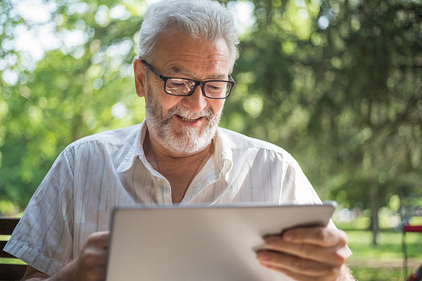 Modern Senior Man With Tablet Photograph by Freemixer