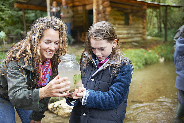 Mom and daughter examining insect in jar Photograph by Adie Bush