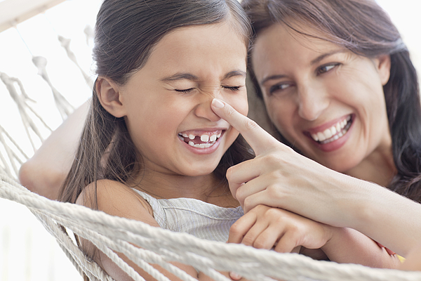 Mother and daughter having fun in hammock Photograph by OJO Images