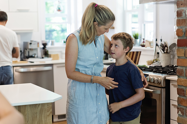 Mother comforting son in home kitchen. Photograph by Martinedoucet