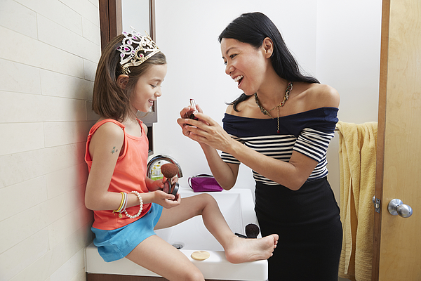 Mother teaching daughter to apply lipstick in bathroom Photograph by Jasper Cole