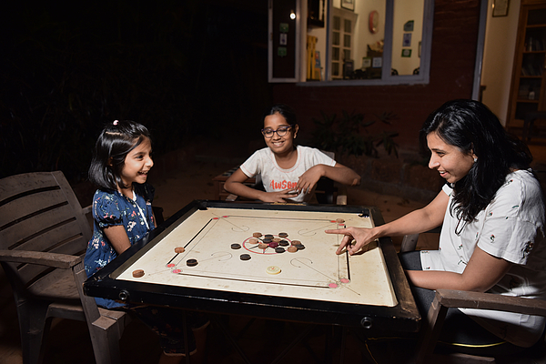 Mother with two daughters playing board game Photograph by Mayur Kakade
