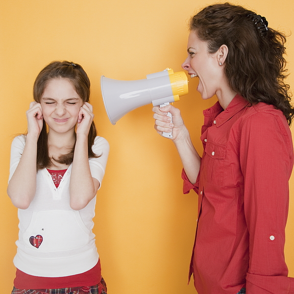 Mother yelling at daughter (10-11 years) through megaphone Photograph by Jamie Grill