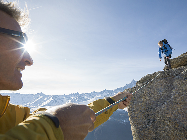 Mountaineer pulls rope tight to teammate, mtns Photograph by Ascent Xmedia