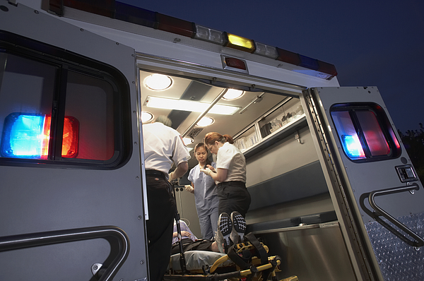 Multi-ethnic medical professionals with patient in ambulance Photograph by ER Productions Limited