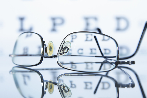 Myopic spectacles with a Snellen eye chart in the background Photograph by GIPhotoStock