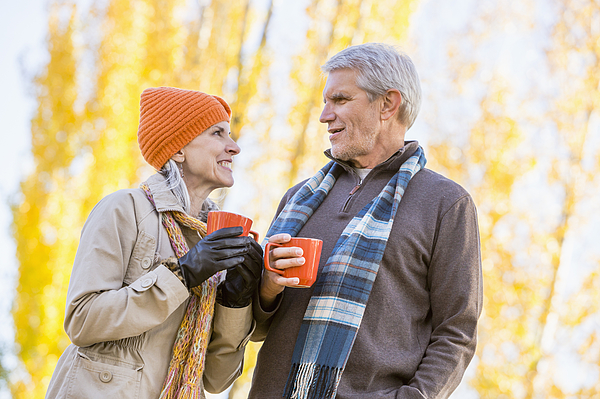 Older Caucasian couple drinking coffee near autumn trees Photograph by Mike Kemp
