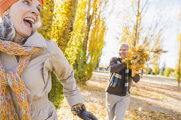 Older Caucasian couple playing with autumn leaves Photograph by Mike Kemp