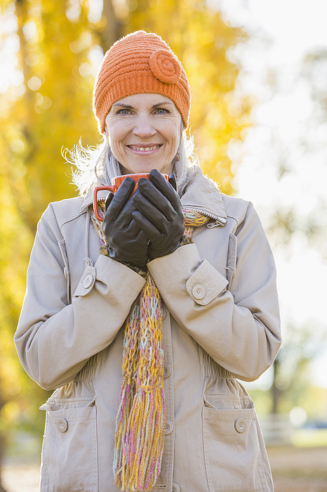 Older Caucasian woman drinking coffee near autumn trees Photograph by Mike Kemp