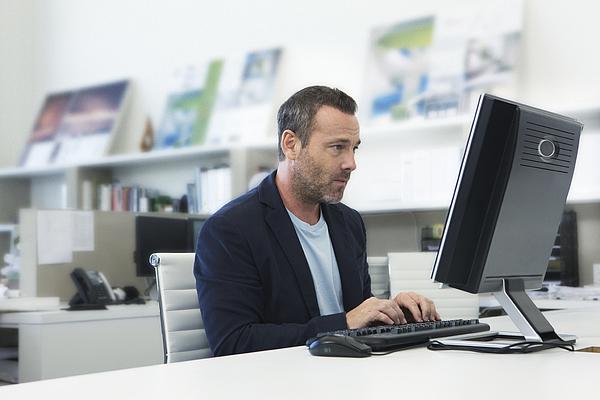 Older Man Working On Computer In Small Modern Offi Photograph by Erik Von Weber
