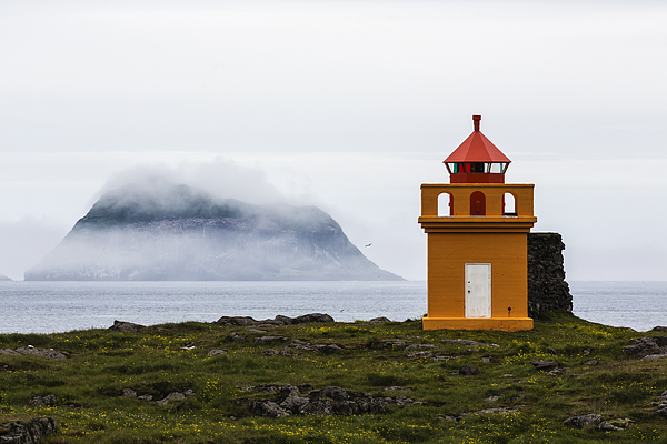 Orange lighthouse on rocky remote cliff Photograph by Jeremy Woodhouse