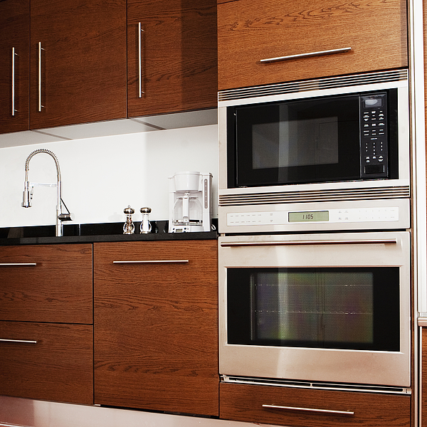 Oven, microwave, cabinets and sink in modern kitchen Photograph by Camilo Morales