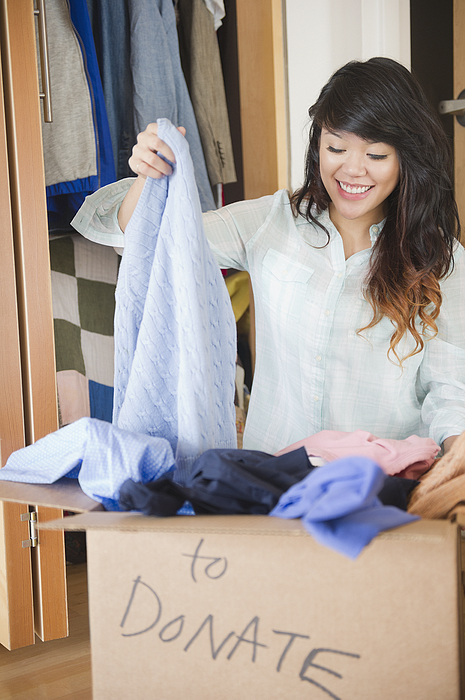 Pacific Islander woman putting donated clothing into box Photograph by JGI/Jamie Grill
