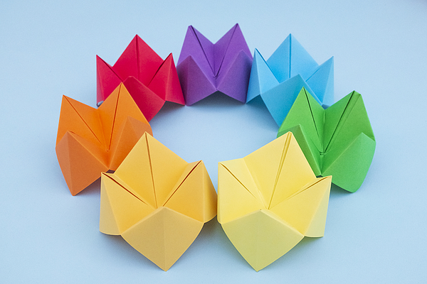 Paper Fortune Tellers arranged by colour on a blue background Photograph by Catherine MacBride