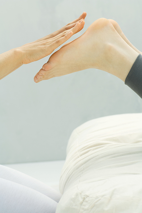 Person performing Reiki foot massage, cropped view Photograph by ZenShui/Milena Boniek