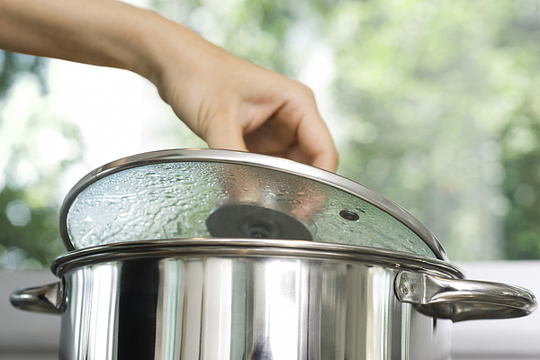 Person removing lid from cooking pot Photograph by PhotoAlto/Laurence Mouton