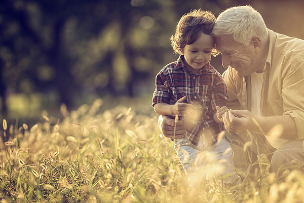 Photo of a cheerful grandfather and his grandson playing outdoors Photograph by Geber86