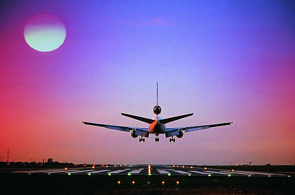 Plane landing on runway Photograph by Digital Vision.