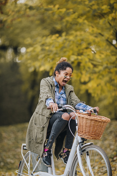 Playful African American woman riding a bicycle and screaming. Photograph by Skynesher