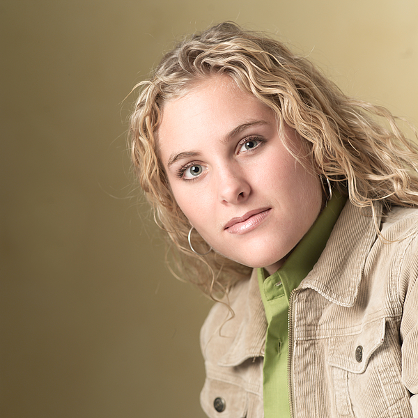 Portrait Of A Blonde Caucasian Teenage Girl In A Green Shirt And Tan Jacket As She Smiles Slightly Photograph by Photodisc