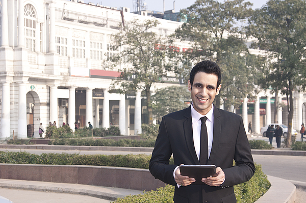 Portrait of a businessman holding a digital tablet , INDIA , DELHI Photograph by IndiaPix/IndiaPicture
