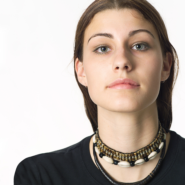Portrait Of A Caucasian Teenage Girl In A Black Shirt Looks Seriously Into The Camera Photograph by Photodisc