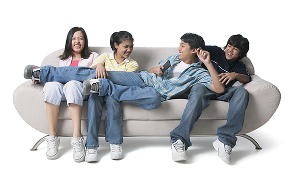 Portrait Of A Group Of Asian Brothers And Sisters As They Sit On The Couch And Fight Over The Remote Control Photograph by Photodisc