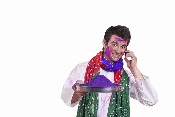 Portrait of a man with holi colour talking on a mobile phone Photograph by IndiaPix/IndiaPicture