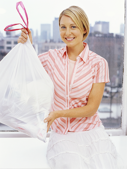 Portrait Of A Mid Adult Woman Holding A Garbage Bag Photograph by Stockbyte