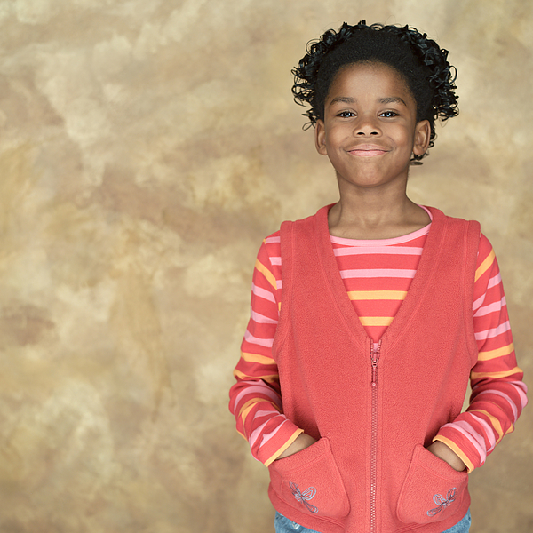Portrait Of A Young African American Girl In A Pink Shirt And Sweater As She Puts Her Hands In Her Pockets And Smiles Photograph by Photodisc