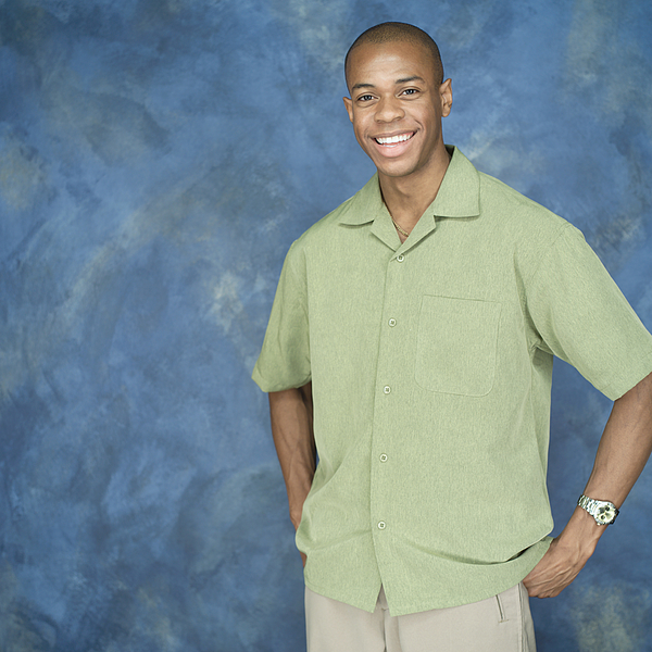 Portrait Of A Young African American Man In A Green Shirt And Tan Pants Puts His Hands On His Hips And Smiles Photograph by Photodisc