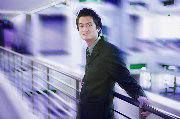 Portrait Of A Young Asian Business Man In A Dark Suit As He Laens Against A Railing Photograph by Photodisc