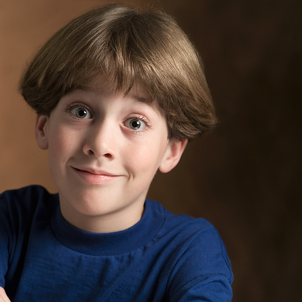 Portrait Of A Young Caucasian Boy In A Blue Shirt As He Flashes A Silly Grin Photograph by Photodisc
