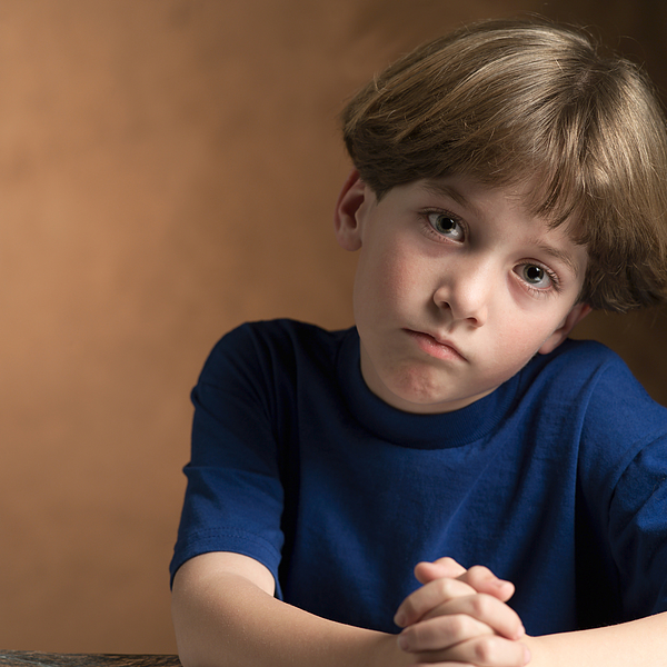Portrait Of A Young Caucasian Boy In A Blue Shirt As He Makes A Sad Face Photograph by Photodisc