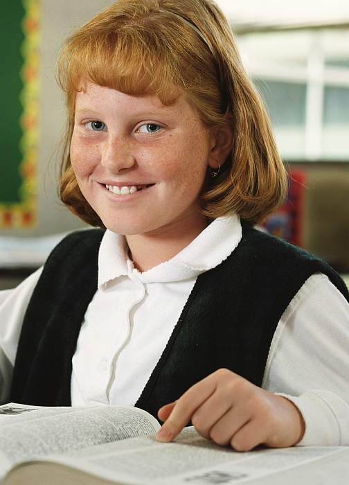 Portrait Of A Young Redheaded Girl As She Sits And Smiles At Her Desk In Her Classroom Photograph by Photodisc