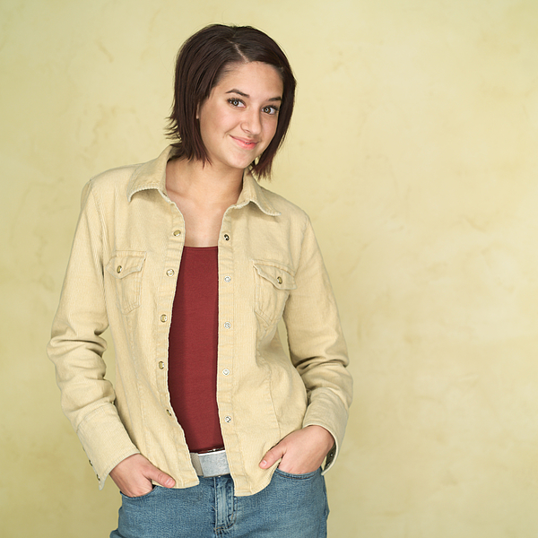 Portrait Of An Ethnic Teenage Girl In A Yellow Jacket As She Puts Her Hands In Her Pockets And Smirks Photograph by Photodisc