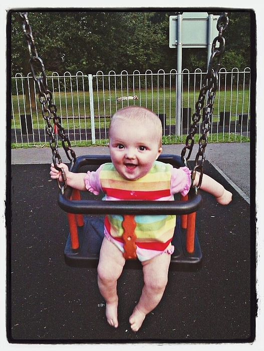 Portrait Of Baby Girl Swinging In Playground Photograph by Leon Radford / EyeEm