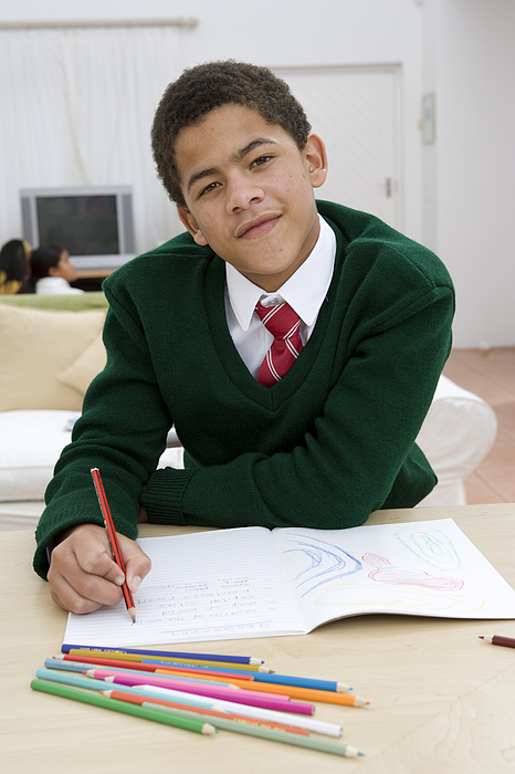 Portrait of boy doing homework Photograph by Alistair Berg