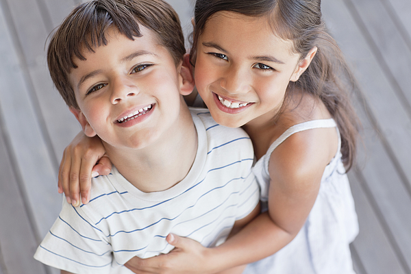 Portrait of brother and sister smiling Photograph by OJO Images
