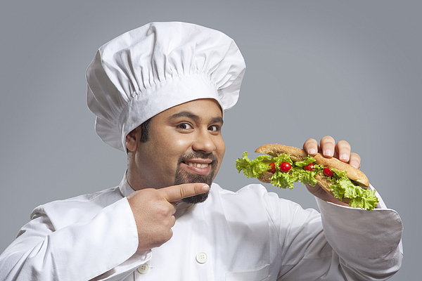 Portrait of chef pointing at sandwich Photograph by Ravi Ranjan
