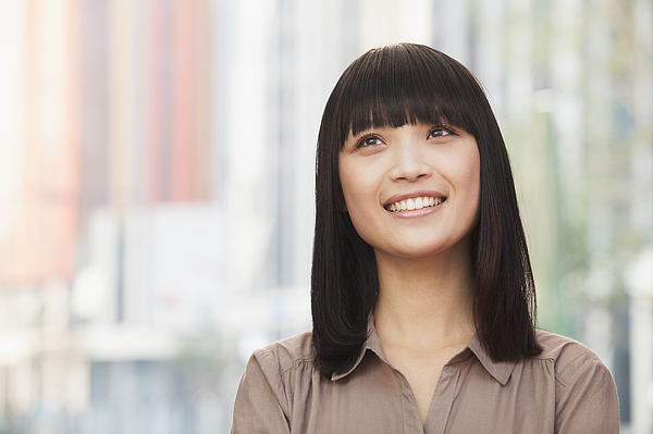 Portrait of smiling young woman outdoors in Beijing, looking up Photograph by XiXinXing