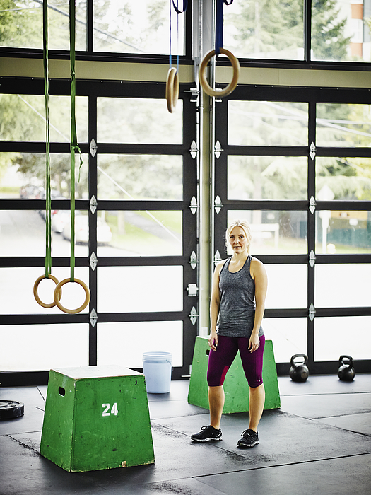 Portrait of woman standing in gym during workout Photograph by Thomas Barwick