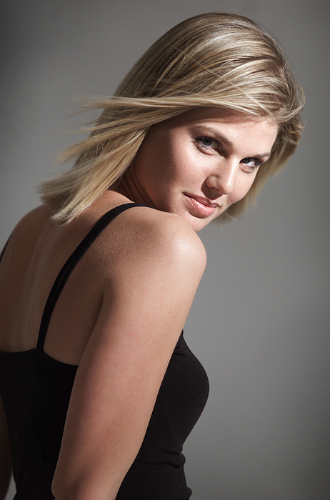 Portrait Of Young Caucasian Blonde Woman In Black Tank Top Looks Over Shoulder Flirts With Camera Photograph by Digital Vision