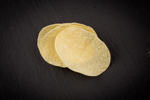 Potato chips on a black Photograph by R.Tsubin