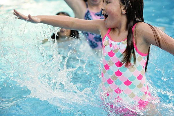 Preteen girl in pool splashing others. Photograph by Martinedoucet